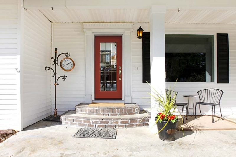White classic porch with a red wooden door